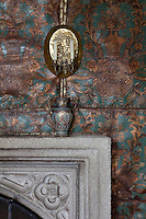 A detail of the embossed leather wall covering around the fireplace, its ornate blue and gold pattern now tarnished with age