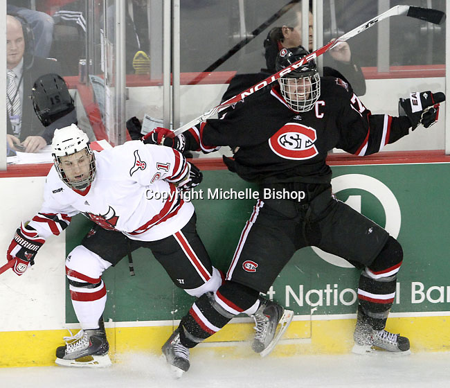 St. Cloud State's Aaron Marvin reacts after slamming into the boards as UNO's Matt White dodges a check. UNO beat St. Cloud State 3-0 Friday night at Qwest Center Omaha.  (Photo by Michelle Bishop)