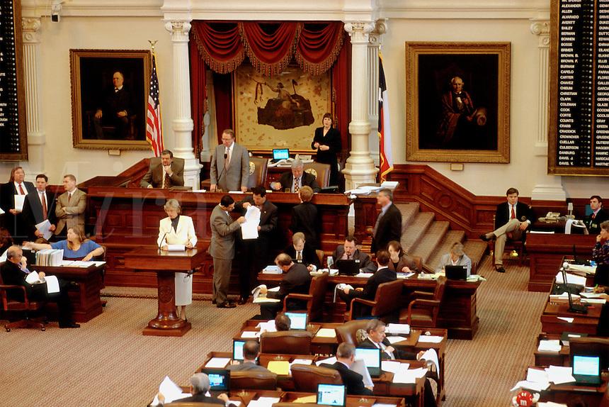 "State government. Texas Legislature. 76th Legislative session. House Speaker James E ""Pete"" Laney (in grey suit on dais). Woman Legislator reads a bill before assembly. Austin Texas."