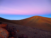 At sunset, people hike along the distant ridgeline of Mauna Kea, Big Island.