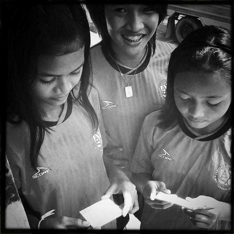 Girls getting ready for soccer, Phnom Penh, Cambodia.