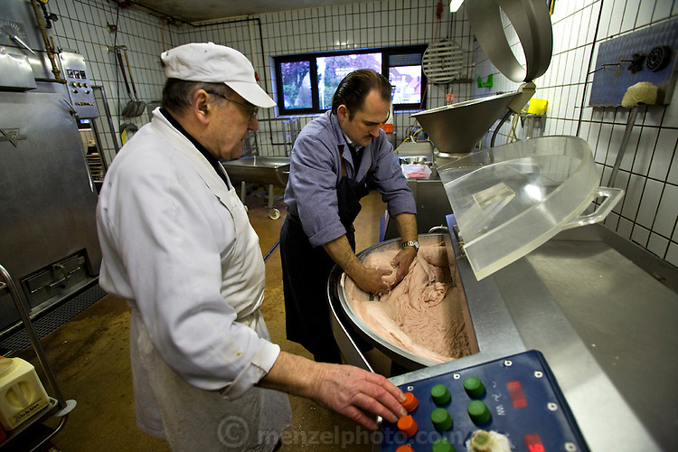 Marcus Dirr (left), a master butcher, makes sausages at his shop in Endingen, near Freiburg im Breisgau, Germany, while his father Peter Dirr, a chief butcher, operates the controls of a mixer. (From the book What I Eat: Around the World in 80 Diets.) The caloric value of his typical day's worth of food in March was 4600 kcals. He is 43 years of age; 5 feet, 9 inches tall; and 160 pounds. The Dirrs know the farmers who supply their animals, and in fact hand choose the animals and watch them grow. MODEL RELEASED.