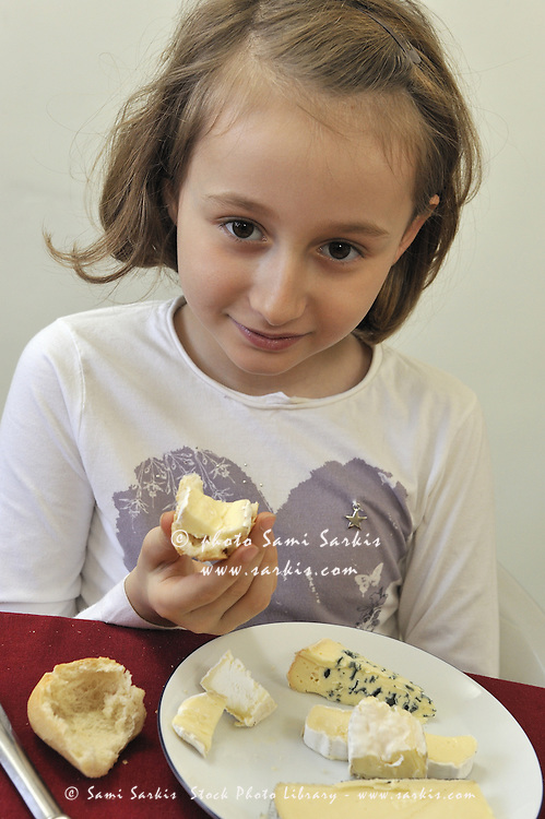 Young french girl (8) having cheese at lunch