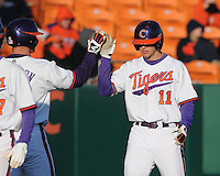 Designated hitter Shane Kennedy (11) of the Clemson Tigers is congratulated after scoring on a Steven Duggar hit in the fifth inning of a game against the Wofford Terriers on Wednesday, March 6, 2013, at Doug Kingsmore Stadium in Clemson, South Carolina. Clemson won, 9-2. (Tom Priddy/Four Seam Images)