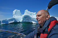 Tour guide Paul Dunphy in front of a large iceberg 6 miles in the Atlantic Ocean<br /> St. Anthony<br /> Newfoundland &amp; Labrador<br /> Canada