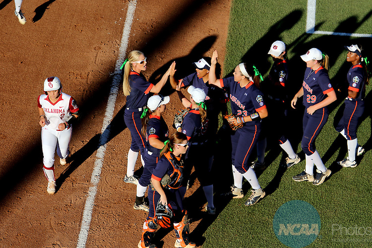 06 JUNE 2016: Auburn University teammates exchange high fives after the end of the first inning against University of Oklahoma during the Division I Women's Softball Championship held at ASA Hall of Fame Stadium in Oklahoma City, OK.  University of Oklahoma defeated Auburn University in Game 1 by the final score of 3-2. Shane Bevel/NCAA Photos