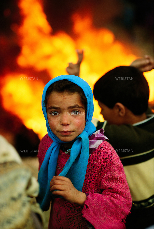 1993. Turkey. Kurdistan. Sirnak Province. Cizre. In answer to the ban of the Turkish government to celebrate Norouz, the Kurdish new year's day, encounters erupted between the population and the Turkish army. Portrait of a Kurdish girl in front of a fire provoked by burned tires. Turquie, Kurdistan, Province de Sirnak, Cizre. En réponse à l'interdiction du gouvernement turc de célébrer Norouz, le nouvel an kurde, des affrontements éclatent entre la population et l'armée turque. Portrait d'une fillette kurde devant un feu provoqué par des pneus brûlés.