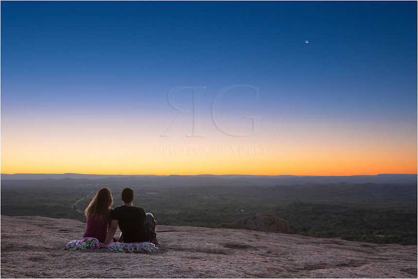 From the top of the granite dome of Enchanted Rock in the Texas Hill Country, a content couple awaits sunrise and the warmth of first light. Thank you to both for allowing me to capture a special moment as the crescent moon rose ahead of the sun on this peaceful morning.<br />