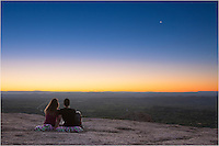 From the top of the granite dome of Enchanted Rock in the Texas Hill Country, a content couple awaits sunrise and the warmth of first light. Thank you to both for allowing me to capture a special moment as the crescent moon rose ahead of the sun on this peaceful morning.<br /> <br /> The walk up from the parking lot at the base of this site is pretty easy and the views are spectacular. If you are ever in the area, this is one location to enjoy the expansive Texas landscape.
