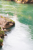 A man standing on a rock fishing in the river Neretva. Historic town of Mostar. Federation Bosne i Hercegovine. Bosnia Herzegovina, Europe.