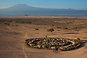 Kenya, near Amboseli, a traditional Maasai manyatta (village) with Kilimanjaro in background