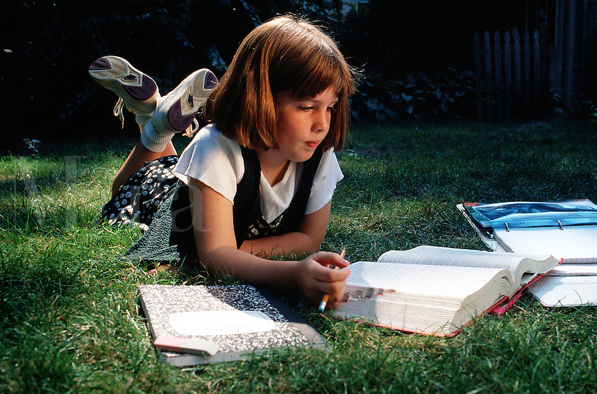 Little girl doing homework outside in the grass.