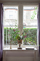 Detail of a vase of lillies in the living room window framed by purple drapes