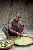 Mikumi, Tanzania. Smiling woman shelling peas in front of a crazed mud wall.