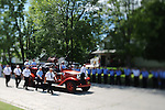 An antique fire truck carries the casket of Pulaski Tri-County Fire Chief Frank Wichlacz in a processional toward the Assumption of the Blessed Virgin Mary church cemetery in Pulaski, Wis., Monday, July 28, 2008. Wichlacz was killed in the line of duty last Wednesday after he was pinned between a parked tanker truck and a pickup truck that crashed into a station bay door while being moved from one parking spot to another at his agency's Glenbrook Avenue fire station.