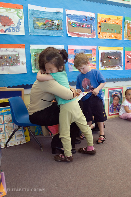 "Berkeley CA  Busy preschool teacher giving out star awards and hugging ""goodbye"" to students."