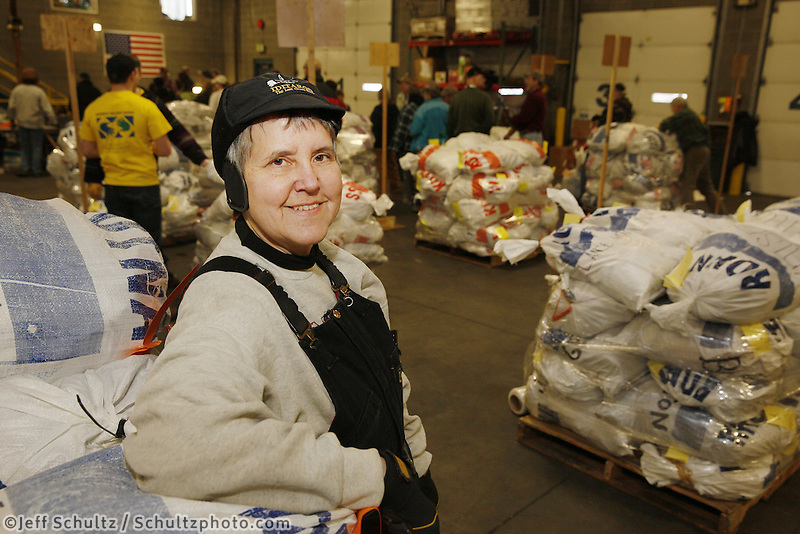 Wednesday, February 13, 2013.   A volunteer for 17 years, Wendy Walters takes a short break on a stack of musher food bags during day one of the food drops at Airland Transport in Anchorage.