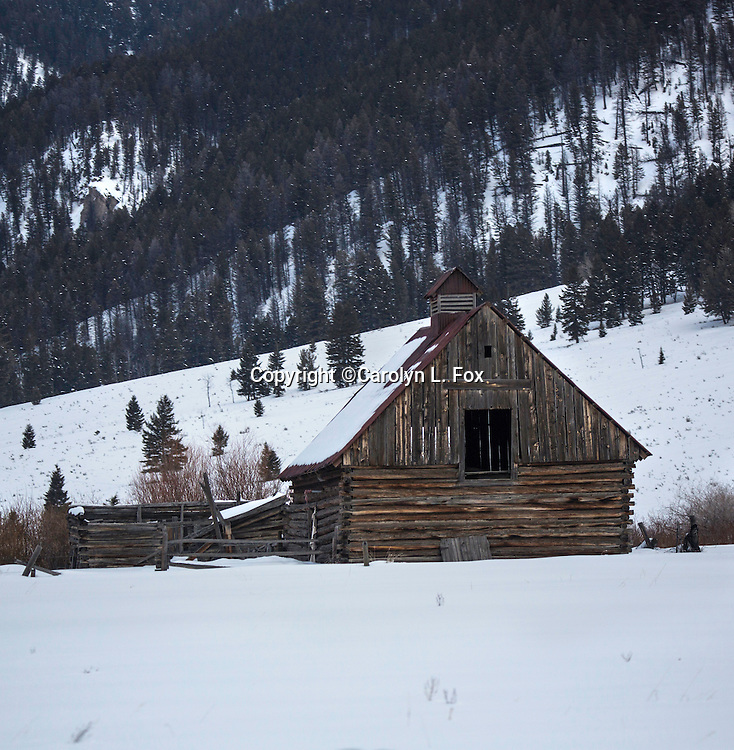 A small barn sits in the snow in the mountains.