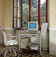 An aluminium trolley and matching swivel chair create a home office in the corner of this living room