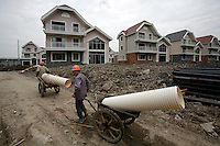 Construction workers walk through a housing development still under construction at the Luodian New Town in Shanghai, China. Designed by the Swedish firm SWECO group, Luodian takes its architectural style from Scandinavia and is one of the nine satellite towns currently planned by the Shanghai government.