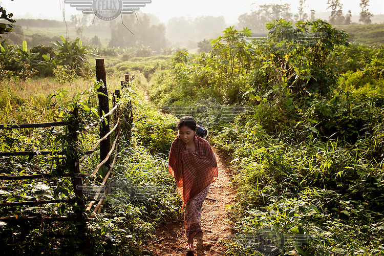 A woman walks along a path through fields outside the village of Padol.