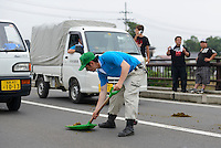 Clearing up horse manure after a parade during the Somanomaoi Festival, Minami-soma City, Fukushima Prefecture, Japan, July 27, 2013. During the four-day-long Somanomaoi Festival members of old samurai families ride horseback through the town in traditional armour.  They also take conduct ceremonies at local shrines, take part in horse races, and compete on horseback to catch a flag launched into the air by fireworks.