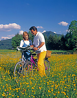 Paar mit Fahrraedern in einer Blumenwiese schauen in Landkarte | couple with bicycles in a flower meadow looking into a map