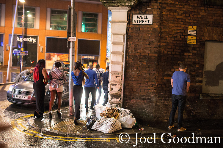 © Joel Goodman - 07973 332324 . 21/12/2013 . Manchester , UK . A man urinates against a wall on Well Street as others walk by . Christmas revellers out in the rain in Manchester on Mad Friday , the last Friday night before Christmas which is typically one of the busiest nights of the year for police and ambulance crews . Photo credit : Joel Goodman