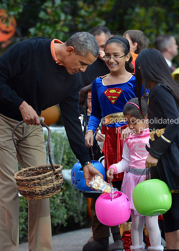 United States President Barack Obama welcomes treat-or-treating local children and children of military families, to the South Portico of the White House, to celebrate Halloween, October 31, 2013, in Washington, DC.    <br /> Credit: Mike Theiler / Pool via CNP