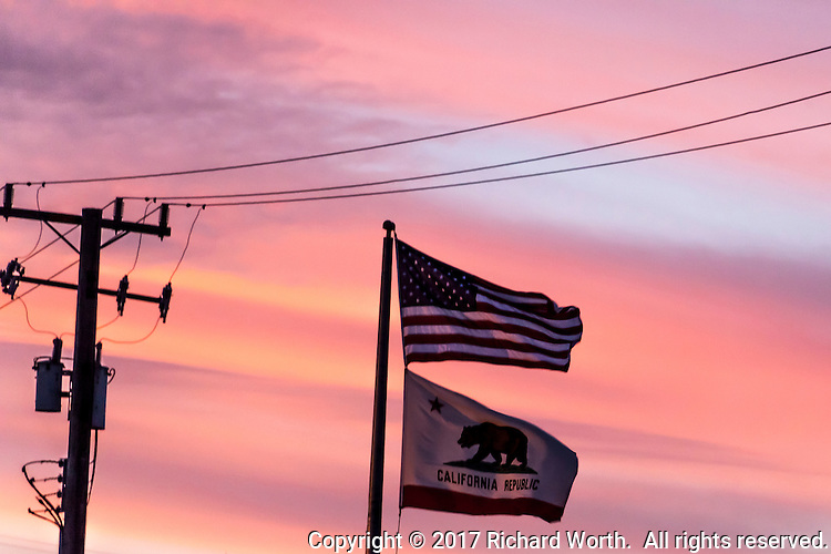The U.S. and California State flags against a sunset sky with a utility pole with power transformers and power lines stretching across the image.
