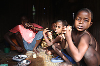 Sera and his 3 boys are eating fish and rice early in the morning. They have a long day ahead as they go to work on the family ricefield situated one hour and a half walk inland from Manompana village. Madagascar, 2012.