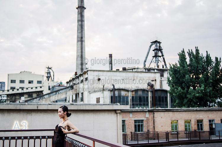 A chinese girl smiles on a terrace in 798 Art District in Beijing, China, July 19, 2014. <br /> <br /> 798 Art District (Chinese: 798艺术区; pinyin: 798 Yìshùqū), or Dashanzi Art District, is a 50-year old decommissioned military factory buildings with unique architectural style. Located in Chaoyang District of Beijing, that houses a thriving artistic community. Since the beginning of 2000, 798 has become a centre for art galleries, artists's ateliers and contemporary arts exhibitions. The buildings are within alleys number 2 and 4 on Jiǔxiānqiáo Lù (酒仙桥路), south of the Dàshānziqiáo flyover (大山子桥). <br /> <br /> © Giorgio Perottino