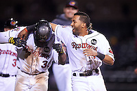 Rochester Red Wings left fielder Adam Walker (30) is mobbed by teammates including Eddie Rosario (1) after a walk off base hit during a game against the Columbus Clippers on June 14, 2016 at Frontier Field in Rochester, New York.  Rochester defeated Columbus 1-0.  (Mike Janes/Four Seam Images)
