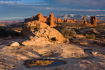A sandstone boulder reflecting in a pothole of water in Arches National Park, near Moab, Utah, with Balanced Rock and the snow-capped La Sal Mountains in the background.