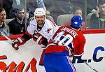 31 March 2010: Carolina Hurricanes' defenseman Jay Harrison is checked by Montreal Canadiens center Maxim Lapierre in the first period at the Bell Centre in Montreal, Quebec, Canada. The Hurricanes defeated the Canadiens 2-1 in their last meeting of the regular season. Mandatory Credit: Ed Wolfstein Photo