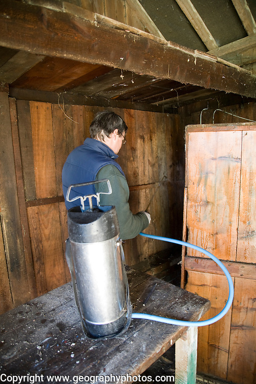Man treating woodworm in a wooden barn with boron spray, UK