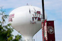 In advance of the fall semester, workers paint the Mississippi State logo on the water tower at the H. H. Leveck Animal Research Center, also known as South Farm. In the foreground, MSU's maroon and white banners hang from a post anchored at the Blackjack Road roundabout.<br />