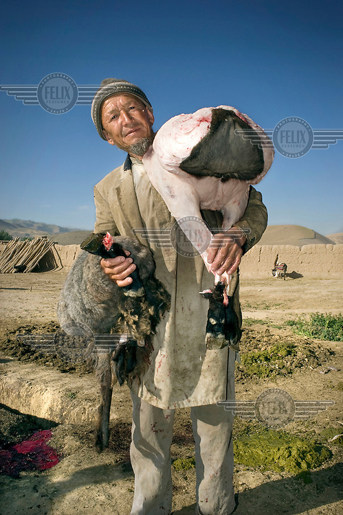 A butcher holds the skin and body of a slaughtered sheep.