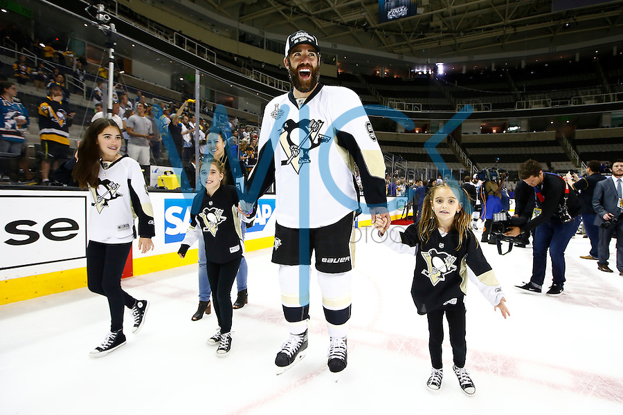 Pascal Dupuis #9 of the Pittsburgh Penguins walks off of the ice with his kids following their 3-1 win against the San Jose Sharks during game six of the Stanley Cup Final at SAP Center in San Jose, California on June 12, 2016. (Photo by Jared Wickerham / DKPS)