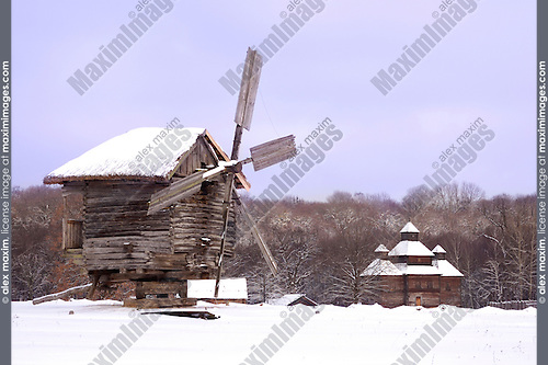 Ancient wooden windmill with a thatched roof covered with snow and a church in a field Ukraine Eastern Europe Winter countryside scenic Horizontal orientation