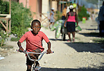 A boy rides a bicycle in Camp Corail, a controversial resettlement of earthquake survivors north of Port-au-Prince, Haiti. Thousands of families were relocated to Corail from flood-prone areas of the capital in 2010, yet the promises of jobs that lured them there failed to materialize.