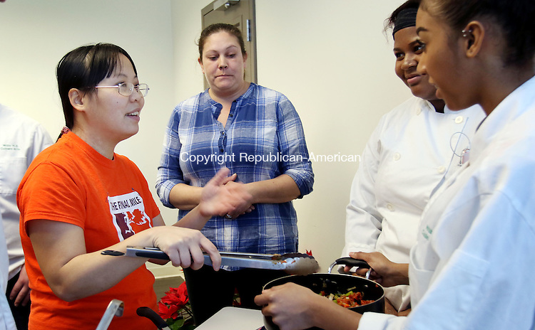 WATERBURY CT. 11 January 2015-011116SV01-From left, Hong Ho and Jennifer Markiewicz both of  Waterbury learn how to cook Vegetable Chili from Nadesia Belcher, 17, and Nanjesia Ventura, 17, both of Wilby High during a Brass City Cooks cooking program for WIC recipients at the Health Department in Waterbury Monday. The Brass City Harvest started the program and they get help from the culinary students from Wilby. <br /> Steven Valenti Republican-American