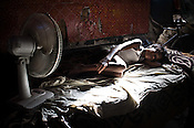 A young boy sleeps behind the vegetable stall of a local market in Govind Puri, New Delhi, India. Photo: Sanjit Das/Panos