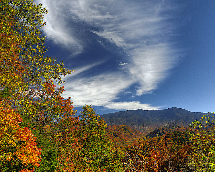 Wind-swept clouds soar over a colorful Fall scene in the Great Smoky Mountains. Three exposure HDR image.