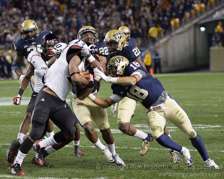 Antwuan Reed (22), Buddy Jackson (21) and Jarred Holley (18) tackle Cincinnati running back Isaiah Pead (23). Cincinnati Bearcats defeated the Pitt Panthers 26-23 at Heinz Field in Pittsburgh, Pennsylvania on November 5, 2011.