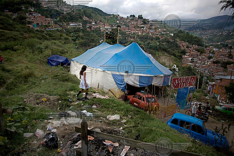 The Konig Circus tent pitched on waste ground in El Salado neighbourhood, a troubled, poor area of the city. Around a dozen small circuses wander the poorer neighbourhoods around the city of Medellin putting on performances in what can be a hand to mouth existence. Despite falling audience numbers, new health and safety regulations and other bureaucracy these small family businesses, many of whom have existed for generations, still scrape a living in a world where the people are more accustomed to being entertained by soap operas than by live entertainment.
