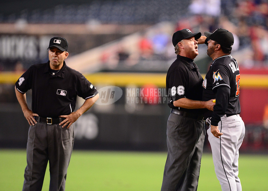 Aug. 22, 2012; Phoenix, AZ, USA: Miami Marlins manager Ozzie Guillen (right) is held back by umpire Jim Joyce as he argues with umpire Angel Campos after being ejected in the third inning against the Arizona Diamondbacks at Chase Field. Mandatory Credit: Mark J. Rebilas-