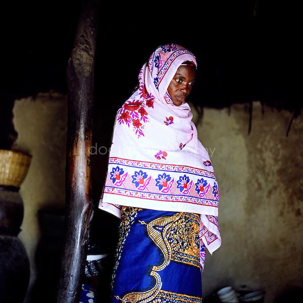 Amina Yahaya is praying in her hut.