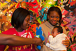 About to have portrait taken at African American Museum, two young sisters, one holding baby nephew in arms, with arm of baby's Mom thrust into scene to try to get baby to look up, at Family Portrait Day, in Hempstead New York, USA, on September 17, 2011. (EDITORIAL USE ONLY)