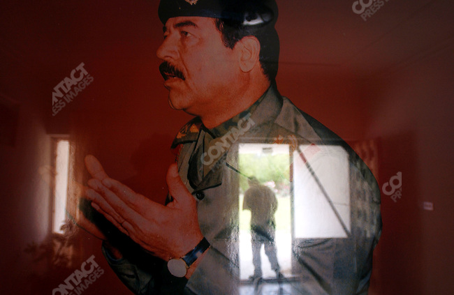A neighbour of the house of Saddam Hussein's mother in the village of Awja just south of TIkrit, where the former Iraqi leader born walked into the front door.  On the walls were still hanging portraits of Saddam Hussein and his family. April 27, 2003
